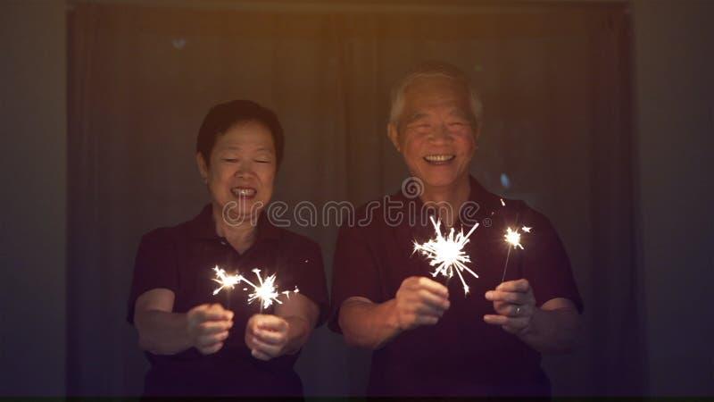 Coppie senior asiatiche che giocano le stelle filante, cracker del fuoco alla notte Concetto che celebra vita immagini stock libere da diritti