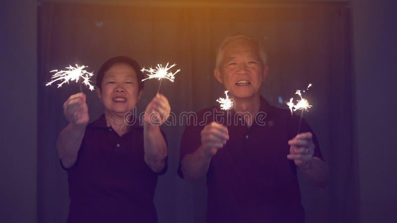 Coppie senior asiatiche che giocano le stelle filante, cracker del fuoco alla notte Concetto che celebra vita immagine stock libera da diritti