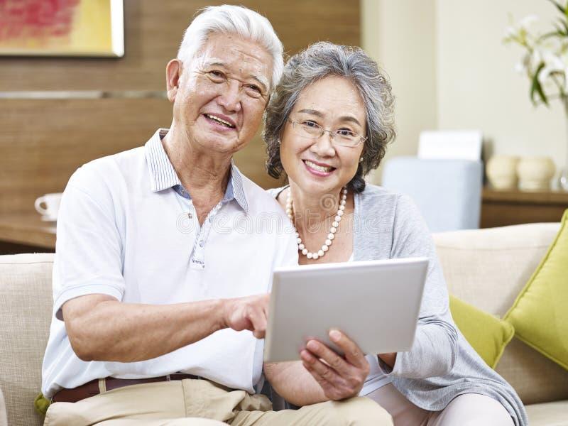 Coppie senior asiatiche felici facendo uso della compressa fotografia stock