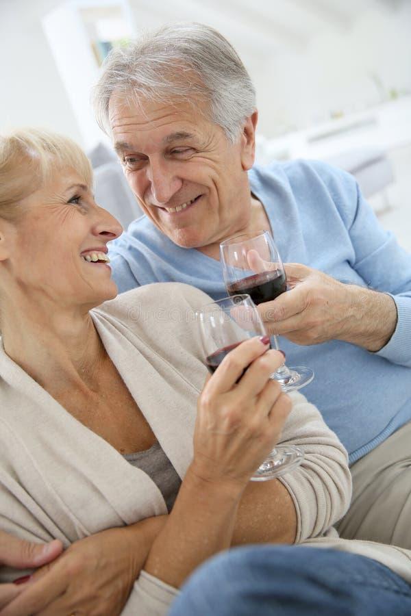 Coppie senior a casa che assaggiano vino rosso fotografia stock