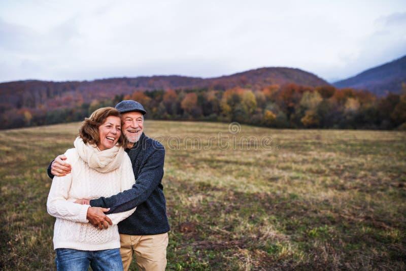 Coppie senior che abbracciano in una natura di autunno al tramonto, ridente fotografia stock libera da diritti