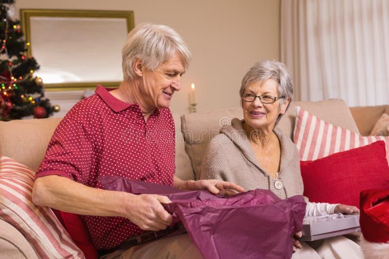 Coppie senior che aprono un regalo di Natale sul sofà immagine stock libera da diritti