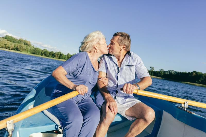 Coppie senior che baciano su una barca fotografia stock
