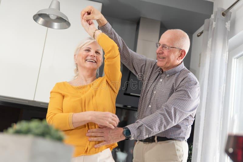 Coppie senior che ballano e che sorridono a casa immagini stock libere da diritti