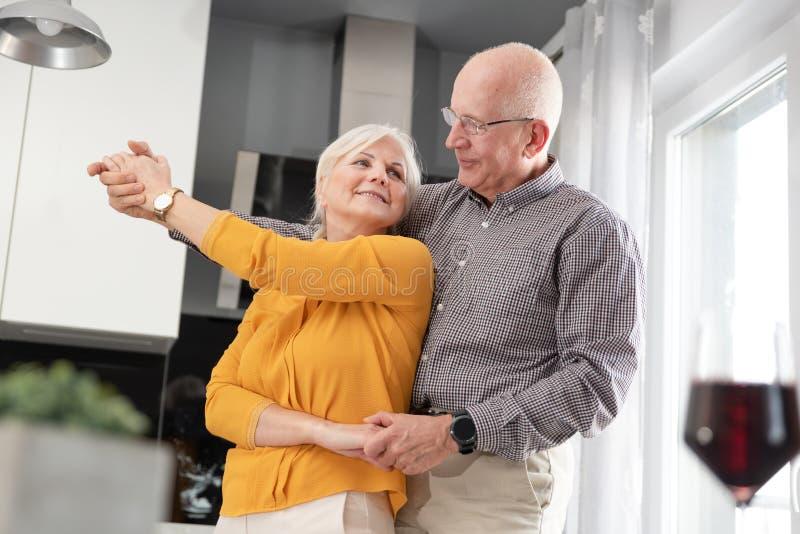 Coppie senior che ballano e che sorridono a casa immagine stock