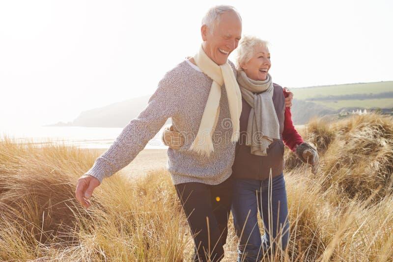 Coppie senior che camminano attraverso le dune di sabbia sulla spiaggia di inverno fotografia stock