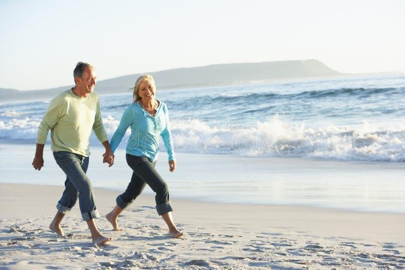 Coppie senior che camminano lungo la spiaggia immagini stock libere da diritti