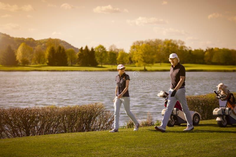Coppie senior che camminano sul campo da golf immagini stock libere da diritti