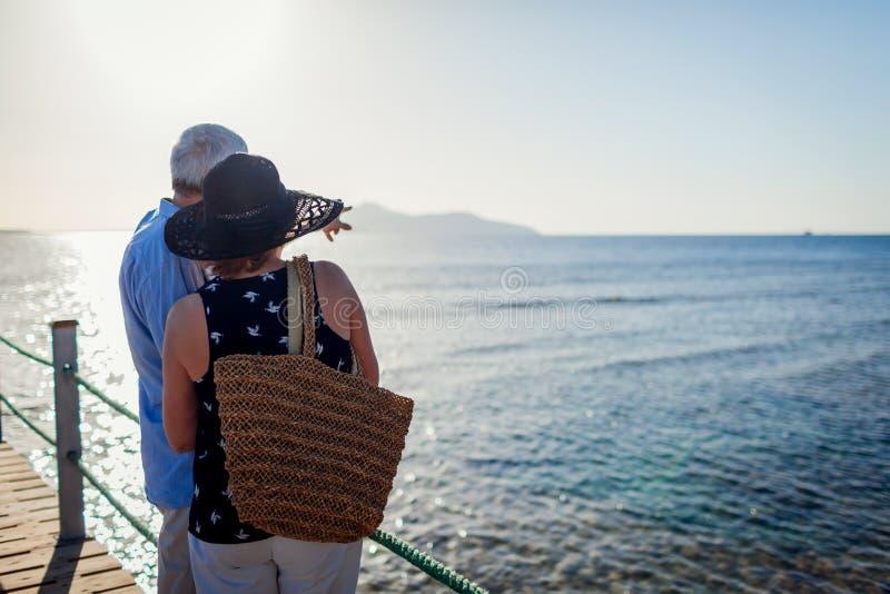 Coppie senior che camminano sul pilastro dal Mar Rosso La gente che gode delle vacanze estive e del paesaggio fotografie stock libere da diritti