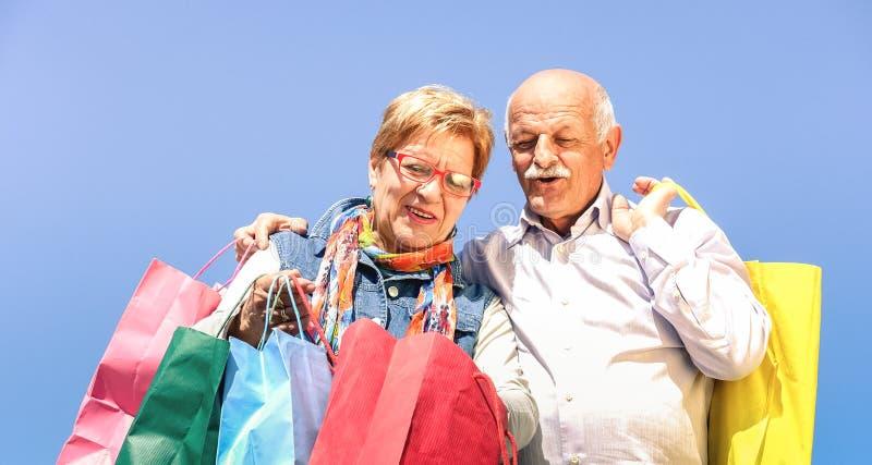 Coppie senior che comperano insieme alla moglie che guarda nelle borse del marito - concetto anziano con divertiresi maturo della fotografie stock