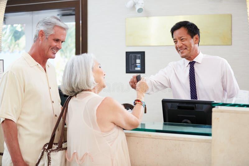 Coppie senior che controllano alla ricezione dell'hotel fotografie stock