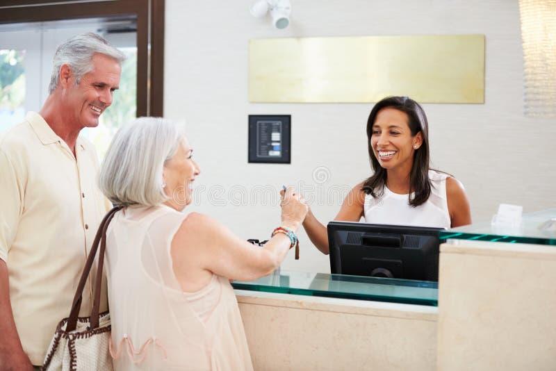 Coppie senior che controllano alla ricezione dell'hotel fotografia stock