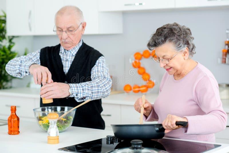 Coppie senior che cucinano e che si divertono nella cucina fotografie stock