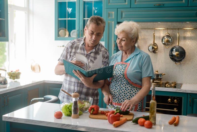 Coppie senior che cucinano un pasto immagini stock