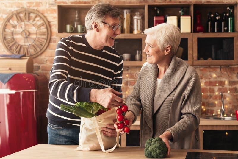 Coppie senior che disimballano i sacchetti della spesa in cucina fotografie stock libere da diritti