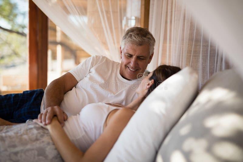 Coppie senior che dormono sul letto del baldacchino immagini stock