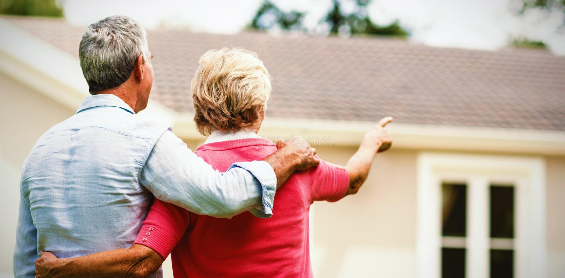 Coppie senior che esaminano casa mentre stando l'iarda del ih immagini stock