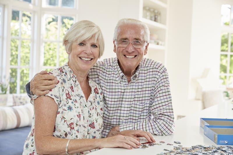 Coppie senior che fanno un puzzle a casa, sorridendo alla macchina fotografica fotografia stock