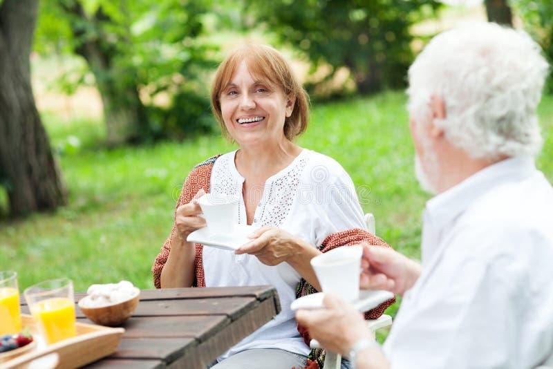 Coppie senior che godono della tazza di caffè all'aperto immagini stock libere da diritti