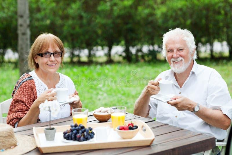 Coppie senior che godono della tazza di caffè all'aperto fotografie stock
