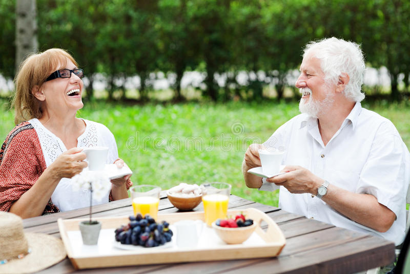 Coppie senior che godono della tazza di caffè all'aperto immagine stock