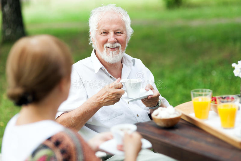 Coppie senior che godono della tazza di caffè all'aperto fotografia stock libera da diritti