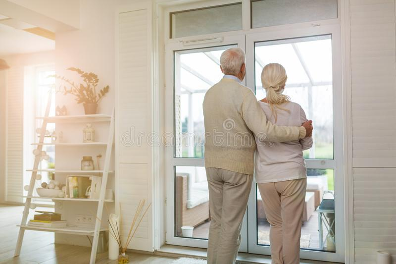 Coppie senior che guardano fuori la finestra del salone fotografia stock