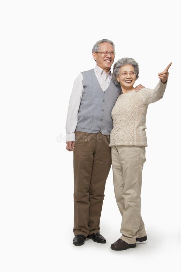 Coppie senior che indicano, colpo dello studio fotografia stock