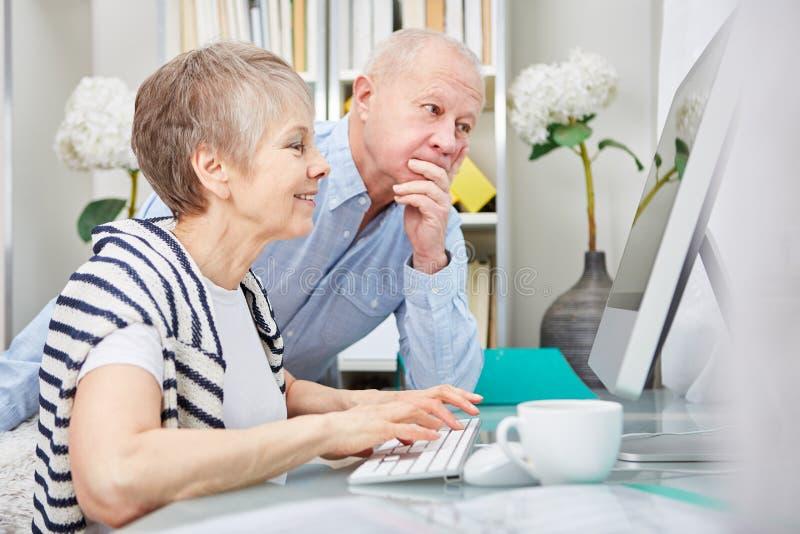 Coppie senior che lavorano con il computer fotografia stock libera da diritti