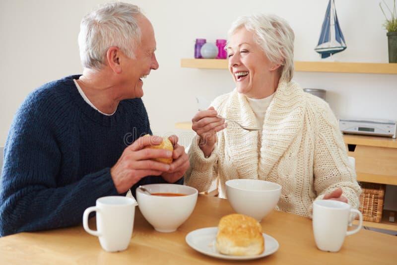 Coppie senior che mangiano ciotola di minestra per pranzo immagini stock