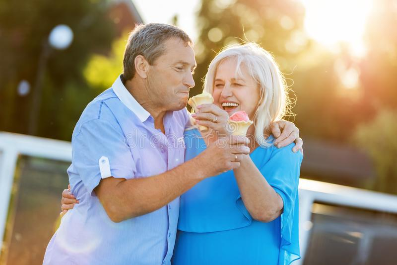 Coppie senior che mangiano il gelato, ridente immagini stock