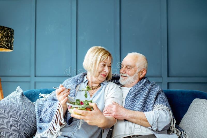 Coppie senior che mangiano insalata sana sullo strato a casa immagini stock