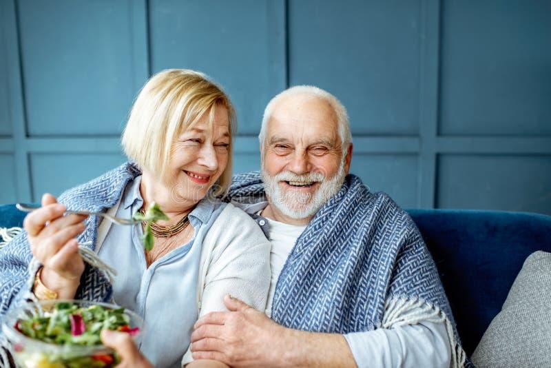 Coppie senior che mangiano insalata sana sullo strato a casa fotografia stock libera da diritti