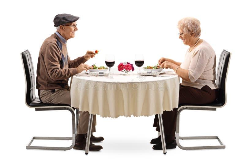 Coppie senior che mangiano un'insalata ad una tavola del ristorante immagini stock