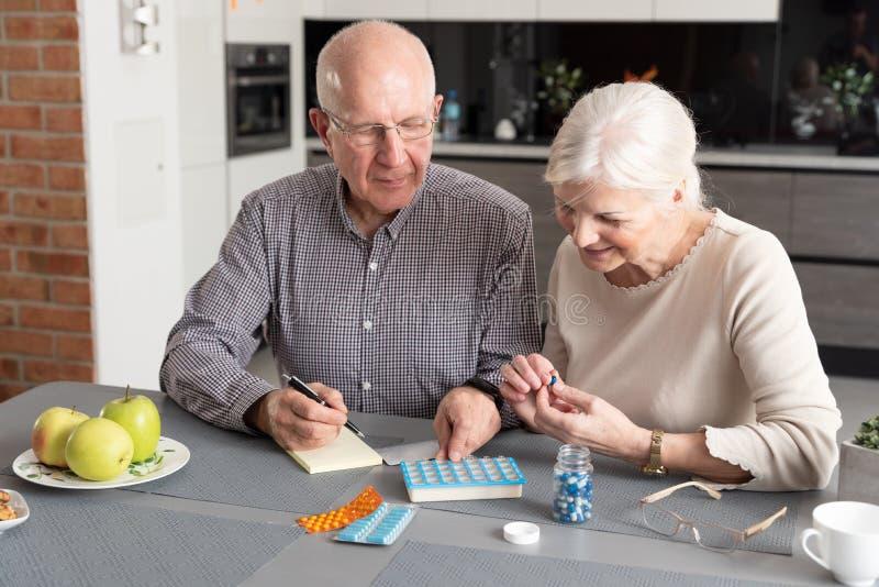 Coppie senior che parlano delle loro medicine immagini stock libere da diritti