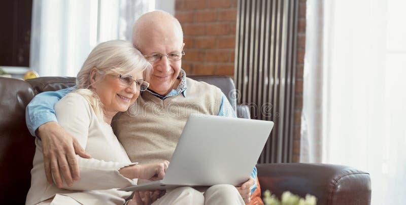 Coppie senior che passano in rassegna insieme Internet fotografia stock