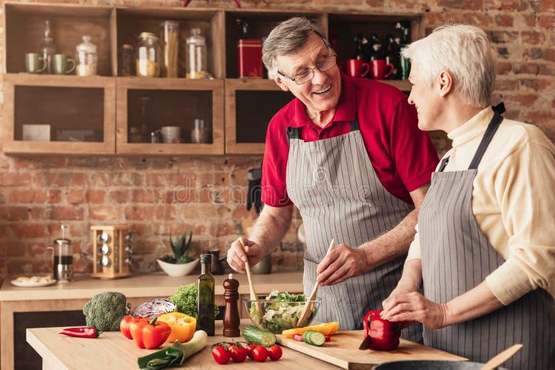 Coppie senior che preparano insalata fresca in cucina fotografie stock
