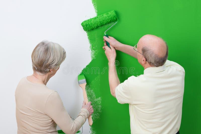 Coppie senior che rinnovano la decorazione interna immagine stock