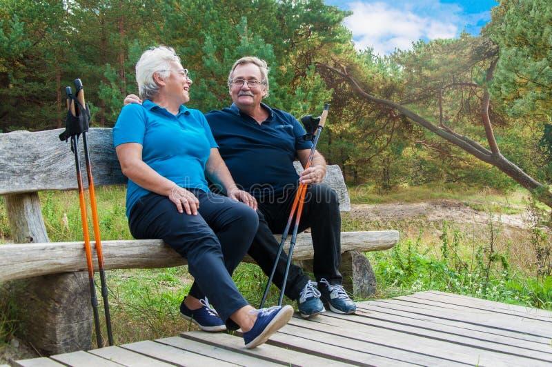 Coppie senior che riposano dopo la camminata nordica immagini stock libere da diritti