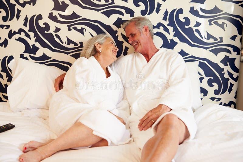 Coppie senior che si rilassano nella camera di albergo immagini stock