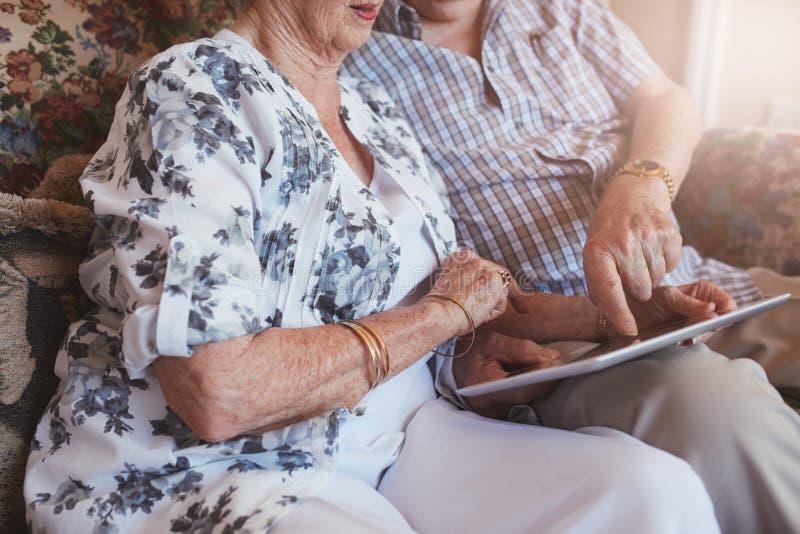 Coppie senior che si siedono insieme facendo uso del computer del touch screen immagini stock libere da diritti