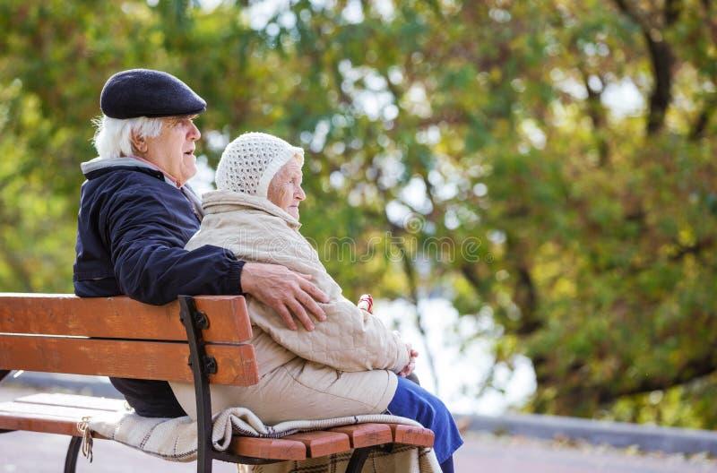 Coppie senior che si siedono sul banco nel parco di autunno fotografia stock