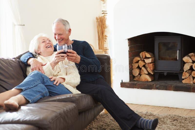 Coppie senior che si siedono sul sofà che beve vino rosso immagini stock