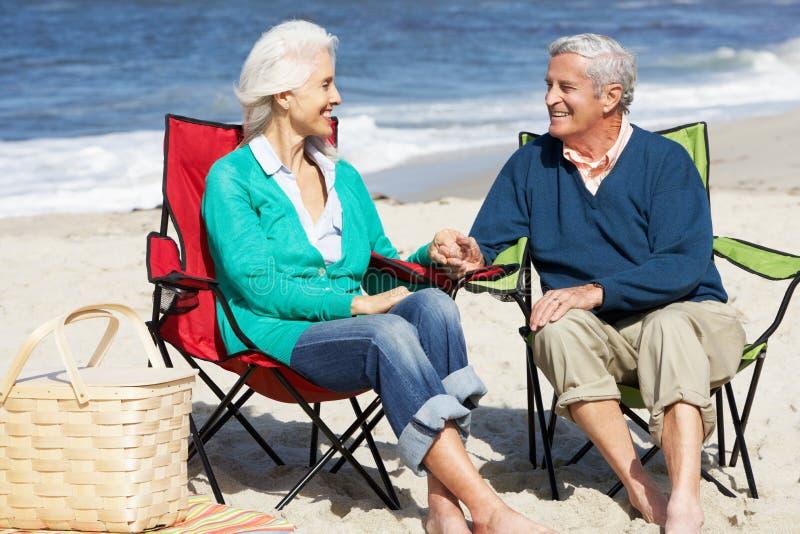 Coppie senior che si siedono sulla spiaggia che ha picnic fotografia stock