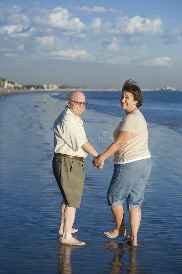 Coppie senior che si tengono per mano alla spiaggia fotografia stock