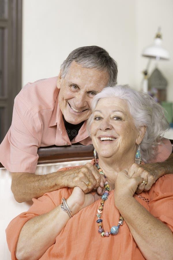 Coppie senior che si tengono per mano nel loro salone fotografia stock libera da diritti
