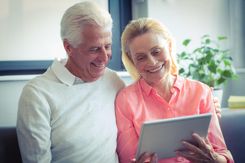 Coppie senior che sorridono mentre per mezzo della compressa digitale immagine stock