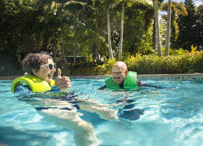 Coppie senior che spruzzano, giocanti e divertentesi ad un parco dell'acqua fotografia stock