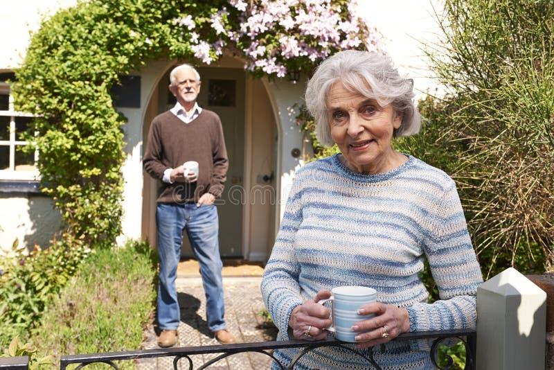 Coppie senior che stanno nel giardino del cottage con le tazze di caffè fotografia stock libera da diritti