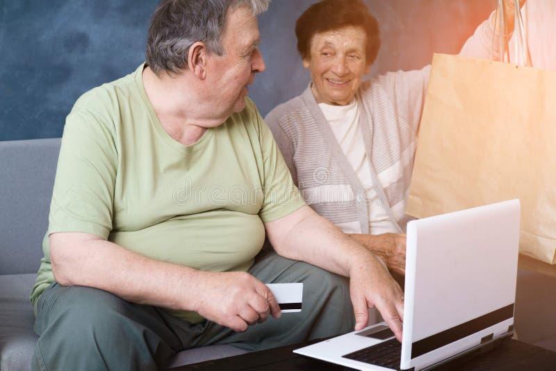 Coppie senior con acquisto del computer portatile al deposito online fotografie stock libere da diritti